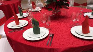 round table decorated in red with white plates and clear glasses