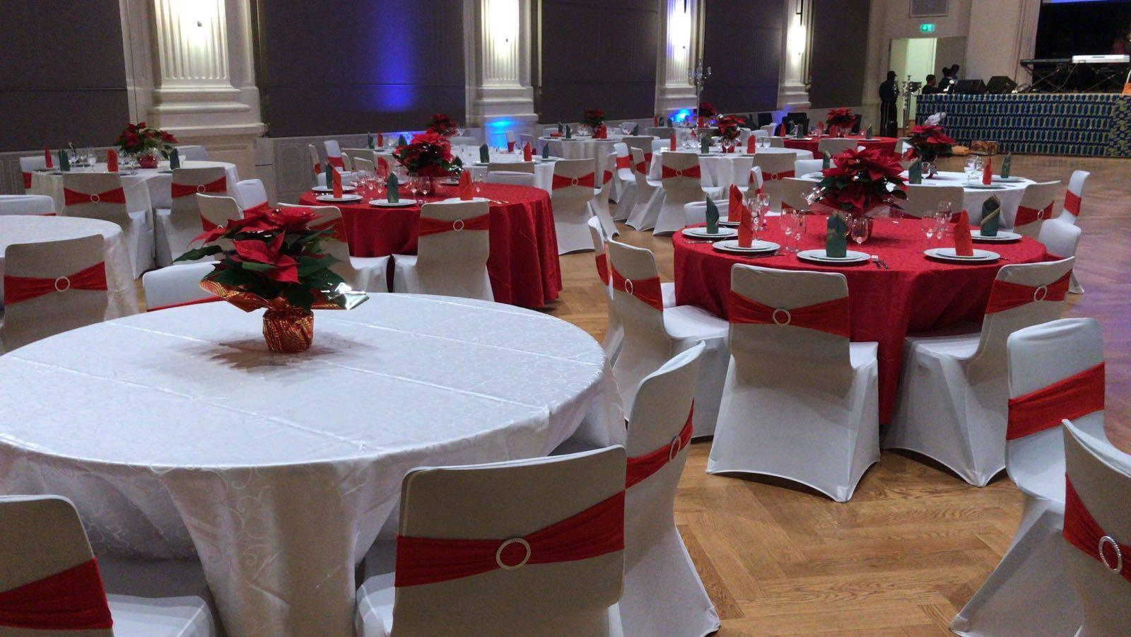 Venue with circular tables decorated in red and white Christmas colors